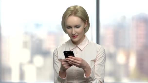 Pretty office woman typing message on her smartphone.