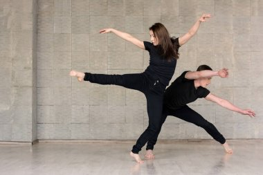 Couple in black suits dancing.