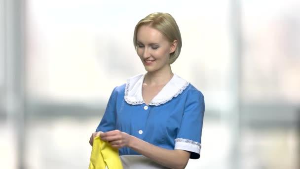 Veselá uklízečka si nasadí rukavice.