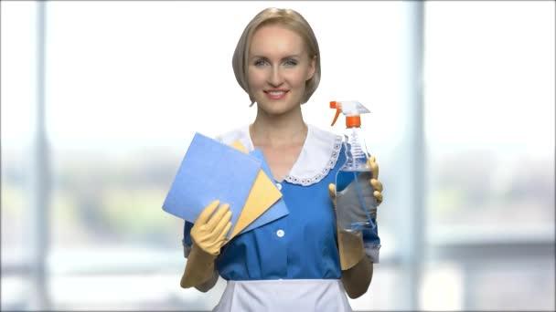 Usmívající se žena ukazuje pracího prostředku a hadr na čištění.
