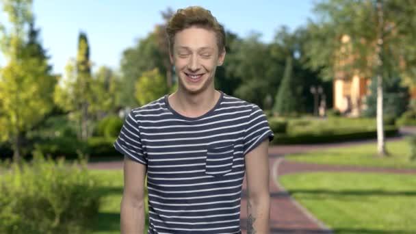 Expresivní teen chlapec se směje venkovní