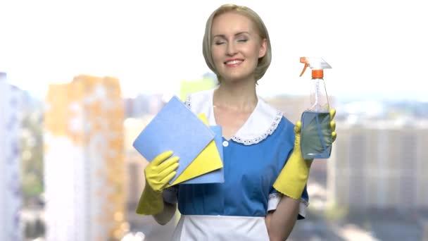 Mladá služka drží hadry a čistící spreje.