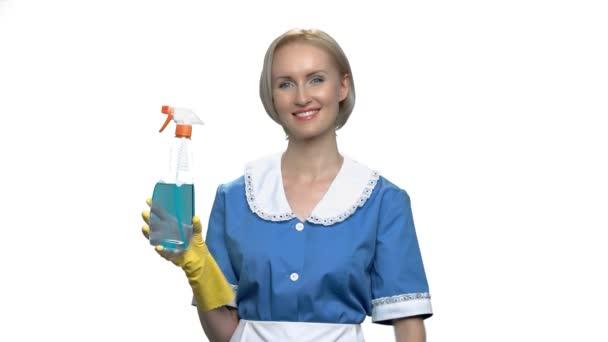 hübsch lächelnde Haushälterin zeigt auf Putzspray.