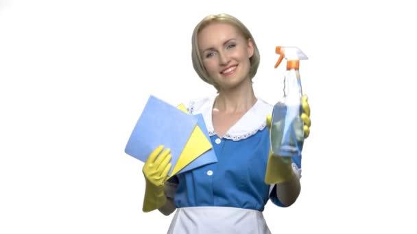 Usmívající se hospodyně v uniformě s hadry a čistící.