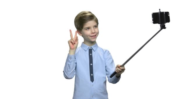 Cute boy showing peace gesture while taking selfie.