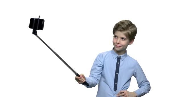 Chlapec s monopod ukazuje obr do fotoaparátu.