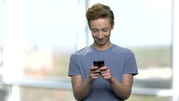 Kavkazská dospívající chlapec pomocí mobilního telefonu