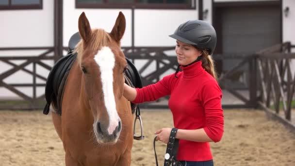 Mladá žena žokej mazlit koně na koňské farmě.