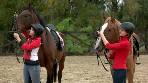 zwei Frauen bereiten Pferde auf dem Hof auf das Reiten vor.