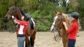 Fotografie Zwei Mädchen bereiten Pferde auf Ranch auf den Ausritt vor.