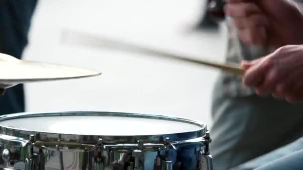 Zenész kezek a dobbottal.