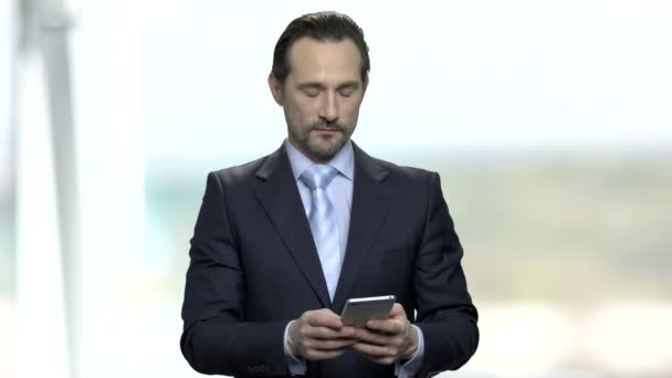 Businessman typing message on his smartphone.