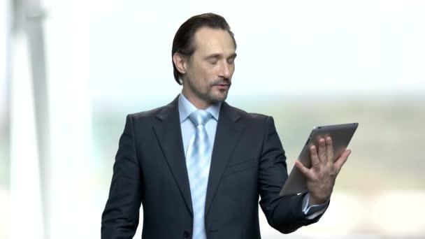 Happy businessman using digital tablet.