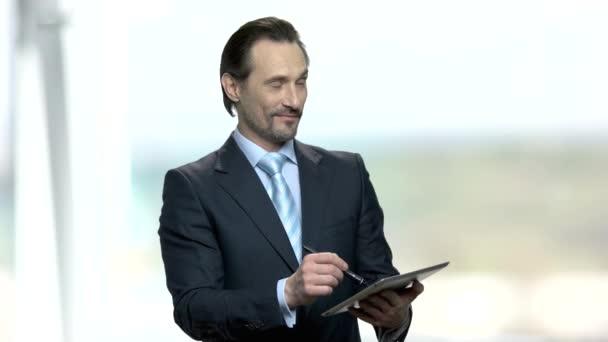Atraktivní obchodník, který si dělá poznámky v tabletu.