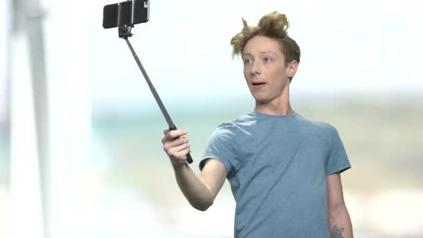 Teenage boy taking selfie using monopod.