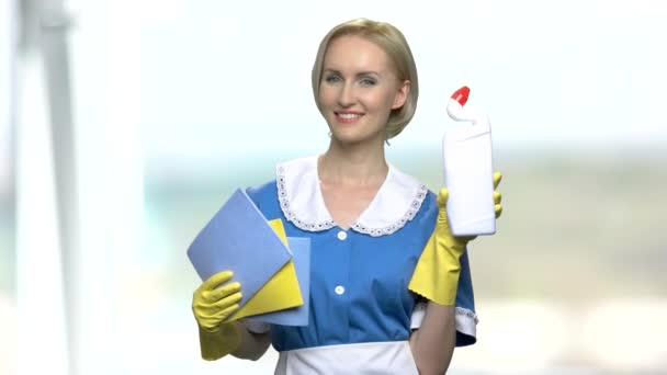 Housekeeper in uniform holding cleaning supplies.