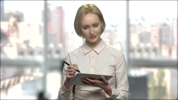 Attractive business woman working on pc tablet.