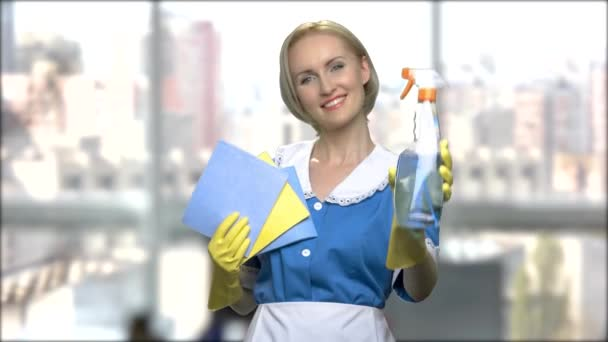Maid in uniform holding rag and cleaning spray.