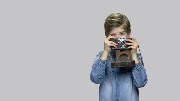 Little boy using old retro camera.