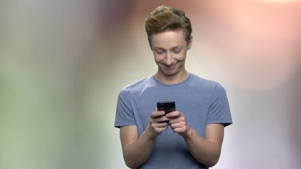 Confused teenage boy using mobile phone.