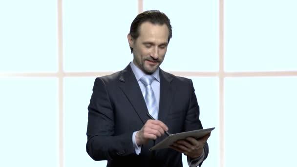 Úspěšný dospělý obchodník s psaním v počítači Tablet PC.
