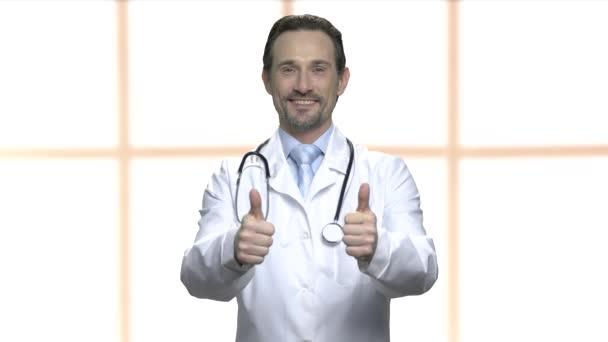 Šťastný dospělý doktor ukazující dva palce.