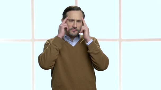 Mature male employee suffering from headache.