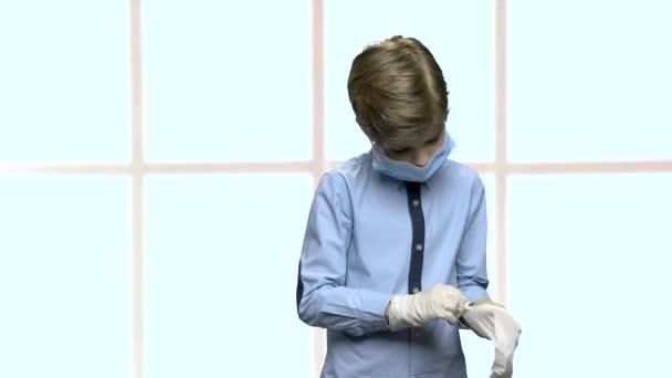 kleiner kaukasischer Junge zieht Gummihandschuhe an.
