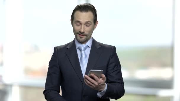 Surprised businessman looking at his smartphone.