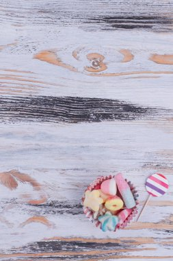 Jelly candies on wooden background.