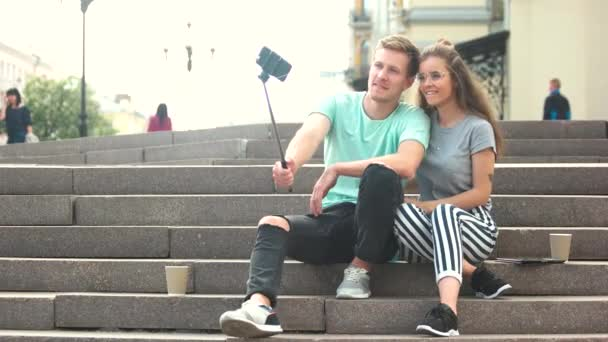 Young trendy couple taking selfie with monopod.