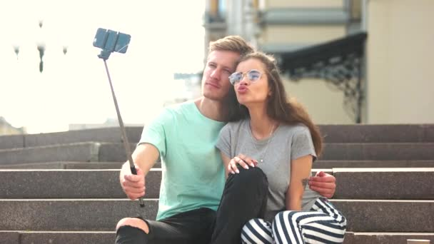 Young trendy couple taking selfie outdoors.