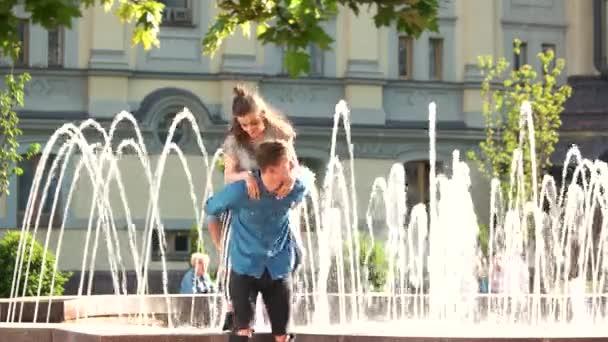 Young cheerful couple having fun near city fountain.