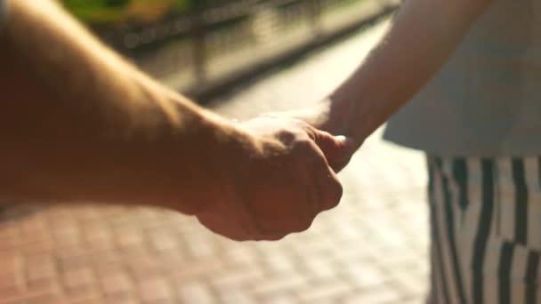 Romantik, který se během letní procházky drží za ruce.