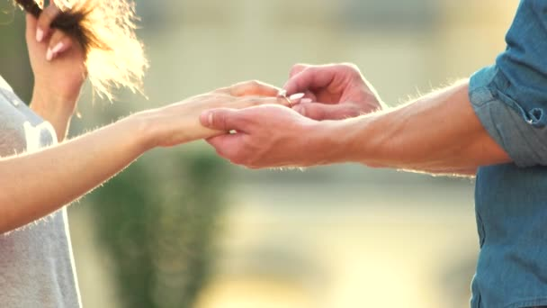 Uomo che mette lanello di fidanzamento sulla mano della donna allaperto.