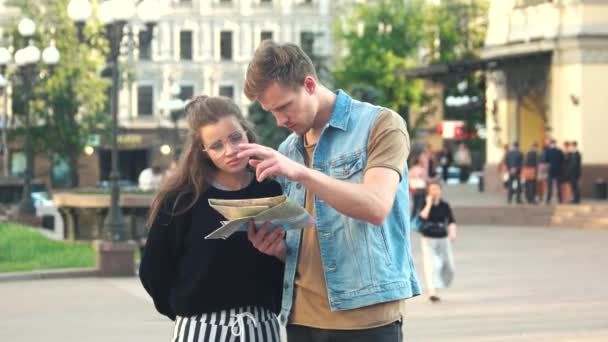 Young stylish couple with map in the city.