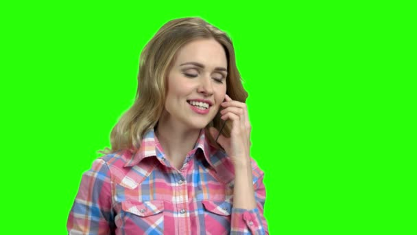 Woman using transparent phone on green screen.