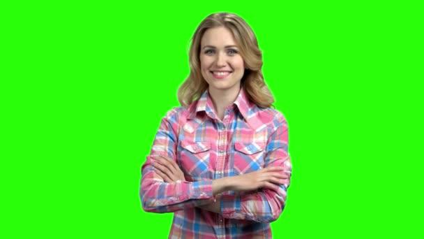 Mosolygó lány keresztbe karokkal zöld képernyőn.