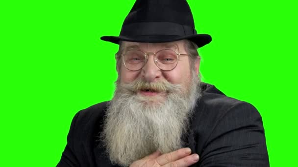 Old bearded man is talking to camera.