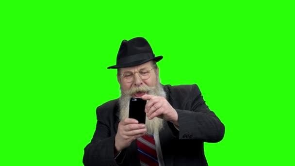 Senior bearded man taking photo with phone.