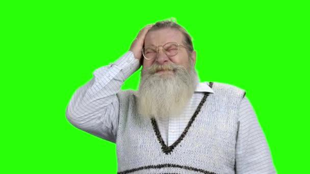 Elderly bearded man having severe headache.