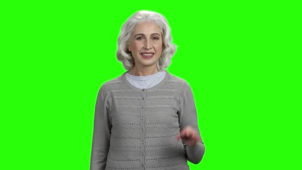 Usmívající se starší žena ukazuje Ok znamení.