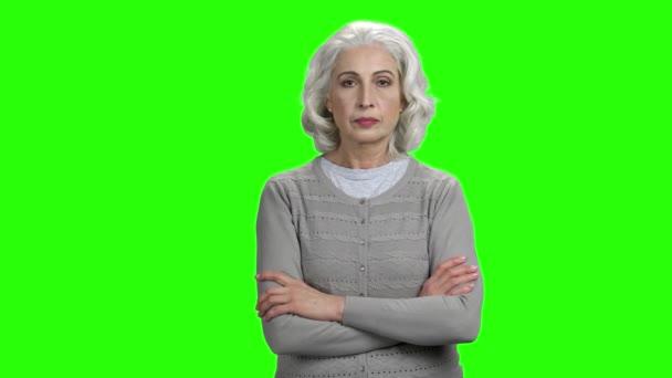 starší žena ukazující Ššš gesto.
