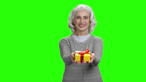 Starší žena poskytující krabici.