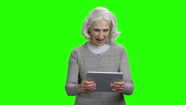 Funny elderly woman playing game on digital tablet.