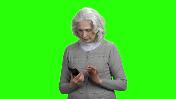 Smiling senior woman with smartphone on green screen.