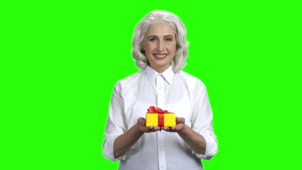 Ajándékdobozt adó nő zöld képernyőn.
