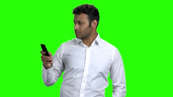 Young man using mobile phone on green screen.