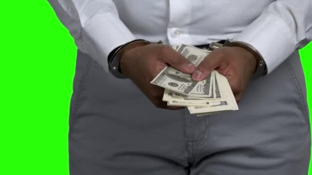 Man in handcuffs holding dollar banknotes.