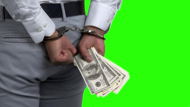 Man in handcuffs holding money, back view.